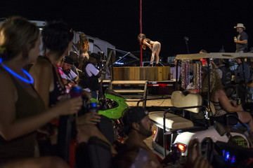 Revelers stop to watch a woman as she pole dances at the Republic of Texas (ROT) Biker Rally in Austin, Texas