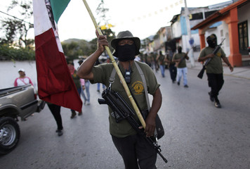 A member of the community police of Guerrero holds up Mexico's national flag as they march to demand the safe return of the missing 43 students of the Ayotzinapa Teacher Training College, in Tixtla