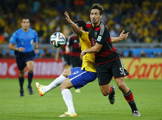 Brazil's Fred fights for the ball with Germany's Hummels during their 2014 World Cup semi-finals at the Mineirao stadium in Belo Horizonte