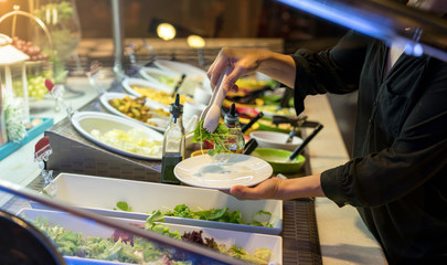 woman hands holding tweezer and dish rocket salad