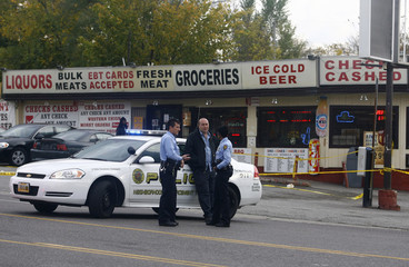 Police gather outside a store where two men who were involved in a shooting were found by police, in Wellston, Missouri