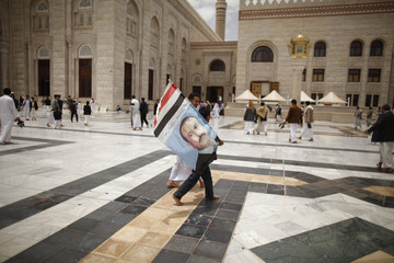A boy holds a flag of Yemen's former President Ali Abdullah Saleh at the al-Saleh mosque in Sanaa