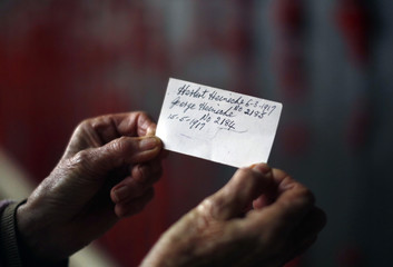 Ada Marchant from Canberra holds a card with names and dates that her uncles Herbert and George Heinecke died in France during World War I, as she visits the Wall of Remembrance on ANZAC Day at the Australian National War Memorial in Canberra