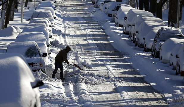 Man digs a car out of the snow on a residential street in the Chicago suburb of Evanston