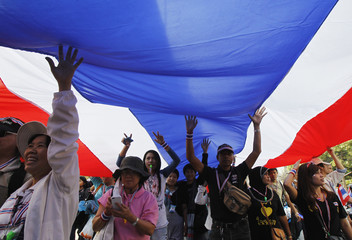 Anti-government protesters hold  a large Thai national flag as they march in a rally at a major business district in Bangkok