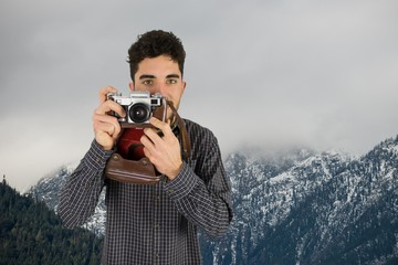 Casual man taking a photo in front of snow-covered mountains
