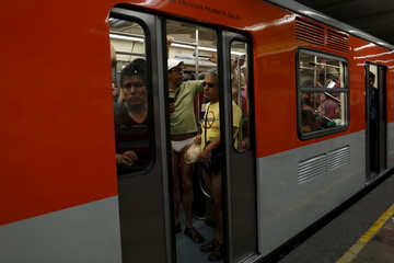 "Passengers not wearing pants stand is a subway train during the ""No Pants Subway Ride"" in Mexico City, Mexico"