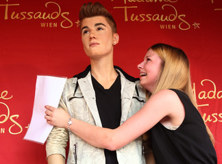 A fan cries after she unveiled a wax figure of pop singer Justin Bieber in Vienna