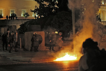 A petrol-bomb explodes near police in front of the parliament building in Athens