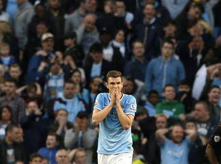 Manchester City's Dzeko reacts after a missed opportunity during their English FA Cup quarter final soccer match against Wigan Athletic at the Etihad stadium in Manchester,