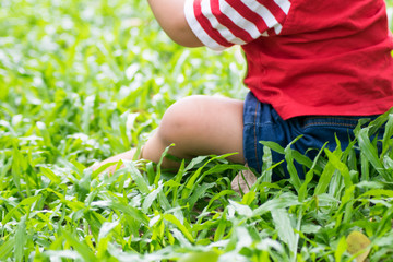 closeup baby girl sitting on green field