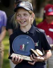Lydia Swan of North East, Pennsylvania holds her awards after she won the Girls 10-11 year-old overall during the Drive, Chip and Putt National Finals at the Augusta National Golf Course in Augusta