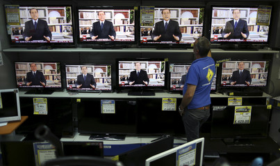 Television sets show Italy's former prime minister Silvio Berlusconi speaking during a pre-recorded nationwide television address, in a store in Rome