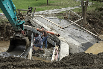People try to fix drain pipes next to a destroyed bridge after a thunderstorm hit the area in Hollenthon