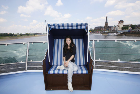 The city of Duesseldorf is seen in the background as Lena of Germany poses for photographers in a beach chair on the deck of a Rhine cruising ship