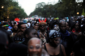 A woman wears devil's horns while marching in the overnight-into-dawn celebration called J'Ouvert, ahead of the annual West Indian-American Carnival Day Parade in Brooklyn, NY