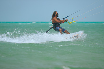 Kite surfer rides waves of the blue lagoon with kite flying in sky. Recreation activity and active extreme water sports kiteboarding, hobby and fun in vacation time, blue sea water, Egypt, Red Sea