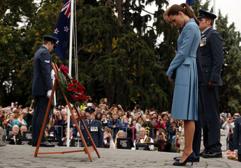 Britain's Prince William and his wife Catherine, Duchess of Cambridge, bow their heads during a ceremony in the town of Blenheim