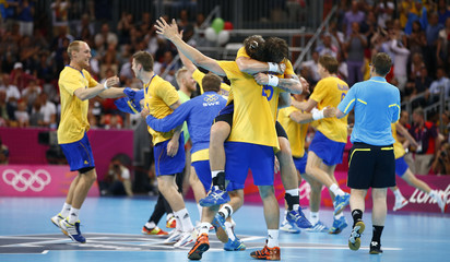 Sweden's team players celebrate after defeating Hungary in their men's semi-final match at the Basketball Arena during the London 2012 Olympic Games