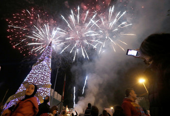 People take pictures of fireworks exploding during a Christmas tree lighting in downtown Beirut,