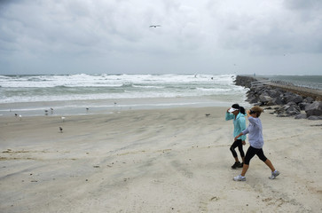 Beachgoers hold on to hats while walking on beach as Hurricane Sandy passes offshore at Lighthouse Point Park in Ponce Inlet