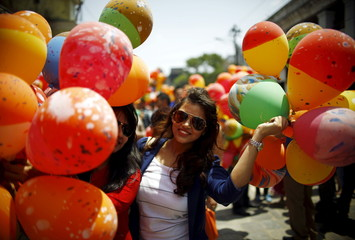 A woman holding balloons poses for a picture before releasing them during an event organized to commemorate the victims of last year's earthquakes in Kathmandu
