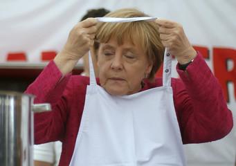German Chancellor Merkel puts on an apron during visit to 'Malteser' mobile kitchen at BBK in Bonn