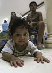 Rokhayah, a one-year-old child from Iraq, and her parents wait in a police station in Surabaya, East Java province