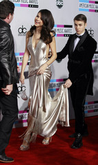 Singer Justin Bieber carries the train of his girlfriend, singer Selena Gomez' dress, as they arrive at the 2011 American Music Awards in Los Angeles