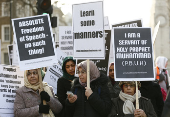 Muslim demonstrators hold placards during a protest against the publication of cartoons depicting the Prophet Mohammad in Charlie Hebdo, near Downing Street in central London