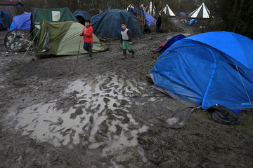 Migrants walk in a muddy field at a camp of makeshift shelters for migrants and asylum-seekers from Iraq, Kurdistan, Iran and Syria, called the Grande Synthe jungle, near Dunkerque