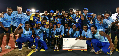 Sri Lanka's team members pose with the trophy after they beat India in the one-day international tri-series final in Dambulla