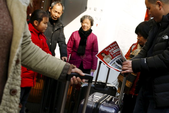 Chinese tourists look at a brochure of a tax free department store in Tokyo