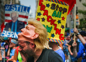 Man wearing a Donald Trump mask wipes sweat from face during protest march on the first day of the 2016 Democratic National Convention in Philadelphia, Pennsylvania