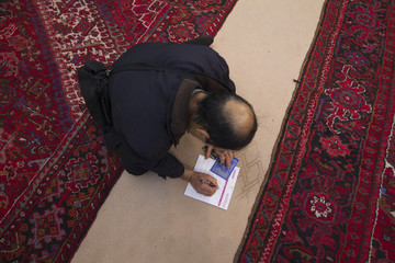 A man writes the names of his candidates in a ballot as he sits in the floor of a mosque, used as a pooling station during Iran's parliamentary election in southern Tehran