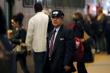 A conductor looks over the platform as a New Jersey Transit commuter train bound for New York City boards passengers at the Secaucus Junction station in Secaucus