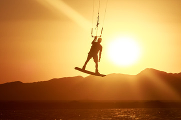 Kiteboarder sportsman with kite under sunset sun, freestyle kiteboarding rider on the evening kitesession, sunset in the sea, extreme watersports, active lifestyle, recreational hobby and fun time
