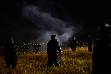 Protesters stand off with police during a protest against plans to pass the Dakota Access pipeline near the Standing Rock Indian Reservation, near Cannon Ball, North Dakota, U.S.