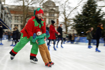 Three year old Henry Butterworth skates with ice marshal Matt Nolan for the camera during whilst ice skating on the rink at the Natural History Museum in London