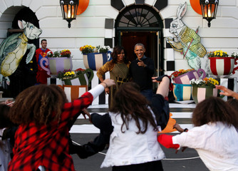 Obama and the first lady react to a flash mob of dancers portraying the zombies from Thriller on the South Portico of the White House in Washington