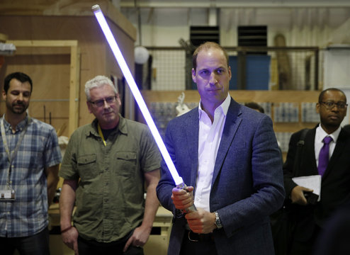 Britain's Prince William holds a light sabre during a visit to the Star Wars film set at Pinewood Studios near Iver Heath, west of London