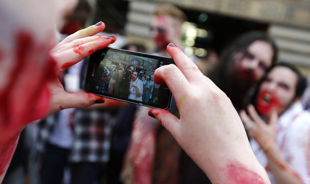 """Participants in the """"Frankfurt zombie walk"""" take pictures of each other as they wait for the start of the event outside the main train station in Frankfurt"""