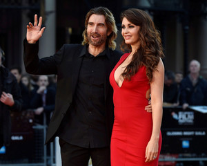 "Sharlto Copley poses with Tanit Phoenix as they arrive for the gala screening of the film ""Free Fire"", during the 60th British Film Institute London Film Festival at Leicester Square in London"