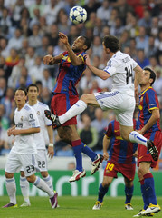 Real Madrid's Xabi Alonso jumps for the ball against Barcelona's Seydou Keita during their Champions League semi-final first leg soccer match at Santiago Bernabeu stadium