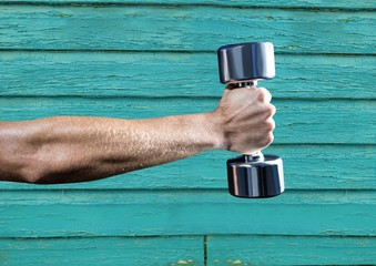 fitness: hand with wight with light blue wood background