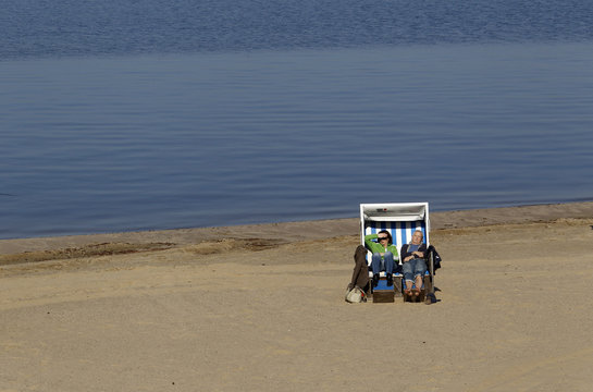 People sit in a beach chair during the first opening day at Berlin's Wannsee lido