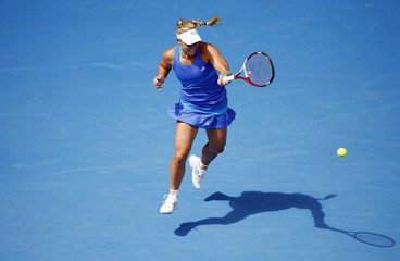 Angelique Kerber of Germany hits a return to Flavia Pennetta of Italy during their women's singles match at the Australian Open 2014 tennis tournament in Melbourne