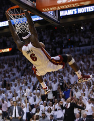 Heat's James swings on the rim after dunking against the Spurs during Game 2 of their NBA Finals basketball playoff in Miami