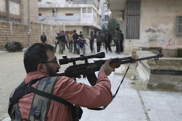 A Free Syrian Army fighter points his weapon during clashes with forces loyal to Syria's President Bashar Al-Assad in Aleppo's Bustan al-Qasr district