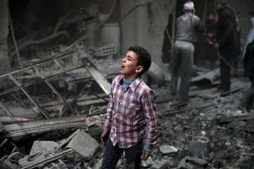 A boy reacts in a site hit by what activists said were airstrikes carried out by the Russian air force in the town of Douma, eastern Ghouta in Damascus, Syria